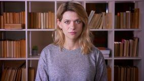 Retrato del profesor rubio de mediana edad que mira tranquilamente y atento en c?mara en fondo de los estantes almacen de metraje de vídeo