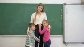 Retrato del profesor sonriente de la sala de clase que abraza con los niños de los principiantes cerca de la pizarra almacen de video