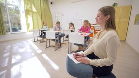 Retrato del profesor sonriente feliz durante la lección en el fondo de los niños jovenes de los alumnos detrás de los escritorios almacen de video