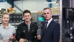 Retrato del propietario de negocio en fábrica con el equipo de la ingeniería almacen de video