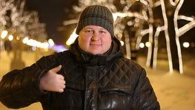 Retrato del pulgar feliz de la demostración del hombre encima del aire libre durante la tarde fría del invierno metrajes