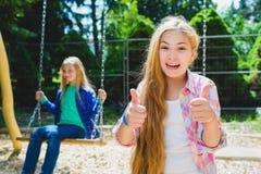 Retrato del pulgar feliz y sonriente de la demostración del niño para arriba en el parque En el fondo la otra muchacha que monta  Imagenes de archivo