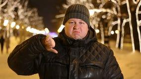 Retrato del pulgar triste de la demostración del hombre abajo del aire libre durante la tarde fría del invierno almacen de video