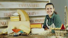 Retrato del queso de tienda atractivo del vendedor Ella mira en la cámara: sonrisa metrajes