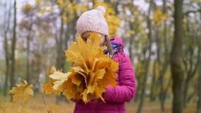 Retrato del ramo de la tenencia del niño de follaje del otoño almacen de video