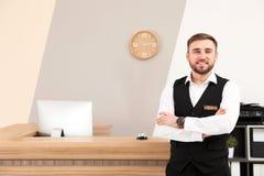 Retrato del recepcionista cerca del escritorio en hotel imagenes de archivo