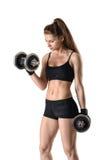 Retrato del recorte de la mujer joven muscular que levanta una pesa de gimnasia para entrenar a su bíceps imagen de archivo