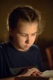 retrato del ` s de la muchacha con el libro en luz reflejada de la vela Imagen de archivo libre de regalías