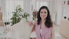 Retrato del sastre de sexo femenino confiado, acertado en la mirada elegante de moda derecha con el maniquí en propio taller de c almacen de metraje de vídeo