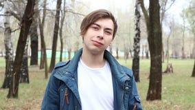 Retrato del signo de la paz feliz caucásico hermoso de la demostración del hombre joven en el parque almacen de video