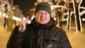 Retrato del signo de la paz feliz de la demostración del hombre al aire libre durante la tarde fría del invierno almacen de video