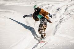 Retrato del snowboarder en la ropa de deportes que monta abajo de la cuesta de la nieve Fotografía de archivo libre de regalías