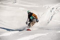 Retrato del snowboarder en la ropa de deportes que monta abajo de la cuesta de la nieve Foto de archivo libre de regalías