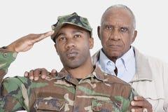 Retrato del soldado de los E.E.U.U. Marine Corps con el padre que saluda sobre fondo gris Fotos de archivo libres de regalías