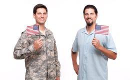 Retrato del soldado y del hombre joven que sostienen banderas americanas Foto de archivo