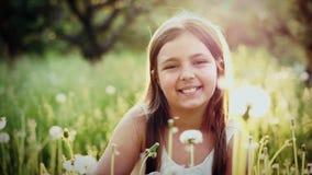 Retrato del soplo lindo de la muchacha en un diente de león en jardín en la puesta del sol almacen de metraje de vídeo