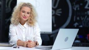 Retrato del teamleader femenino joven acertado que tiene sentada interior del buen tiempo en la tabla almacen de metraje de vídeo
