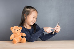 Retrato del teléfono elegante del uso asiático de la niña Imagen de archivo