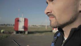 Retrato del trabajador del aeropuerto que habla en la radio portátil en cierre para arriba almacen de metraje de vídeo