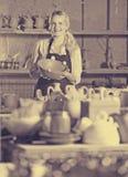 Retrato del trabajador alegre de la cerámica de la mujer con loza de cerámica imágenes de archivo libres de regalías