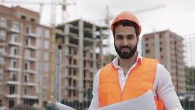 Retrato del trabajador de construcción en el casco anaranjado que mira la cámara El constructor con los soportes del proyecto de  almacen de video