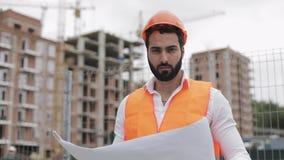 Retrato del trabajador de construcción en el casco anaranjado que mira la cámara El constructor con los soportes del proyecto de  almacen de metraje de vídeo