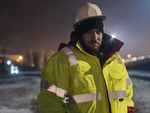 Retrato del trabajador de construcción joven en casco en la noche Imagenes de archivo