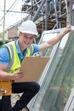 Retrato del trabajador de construcción Preparing To Fit nuevo Windows Imagen de archivo