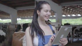 Retrato del trabajador de sexo femenino bonito joven en la granja de la vaca que comprueba proceso de trabajo, usando su tableta  almacen de video