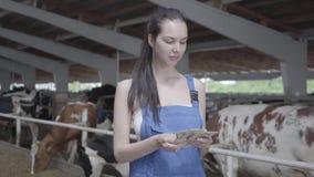 Retrato del trabajador de sexo femenino bonito joven en la granja de la vaca que cuenta la sonrisa del dinero El granjero positiv almacen de video