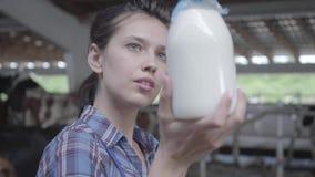Retrato del trabajador de sexo femenino joven en la granja de la vaca que comprueba la calidad de la leche en el primer de la bot metrajes