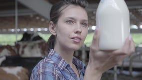 Retrato del trabajador de sexo femenino joven en la granja de la vaca que comprueba la calidad de la leche en el primer de la bot almacen de metraje de vídeo