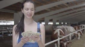 Retrato del trabajador de sexo femenino lindo joven del granjero en la granja de la vaca que cuenta efectivo El granjero positivo metrajes