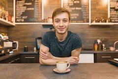 Retrato del trabajador de sexo masculino sonriente joven del café, colocándose en el contador Hombre con las manos dobladas con c imagen de archivo libre de regalías