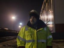 Retrato del trabajador joven del almacén en casco en la noche Imagen de archivo