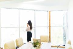 Retrato del trabajador joven que habla usando el teléfono celular, mirando hacia fuera la ventana Femenino teniendo llamada del n Fotografía de archivo libre de regalías