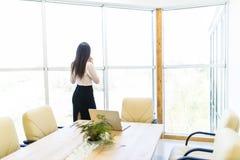 Retrato del trabajador joven que habla usando el teléfono celular, mirando hacia fuera la ventana Femenino teniendo llamada del n Foto de archivo libre de regalías