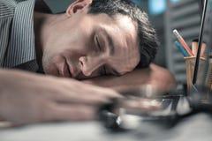 Retrato del trabajador soñoliento que pone en una tabla foto de archivo libre de regalías