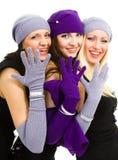 Tres mujeres en blanco hacen punto el sombrero y las manoplas de las lanas Fotografía de archivo