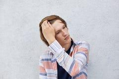 Retrato del varón apuesto con el peinado de moda que lleva a cabo su mano en el pelo que mira a un lado con la expresión soñadora Fotos de archivo libres de regalías