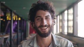 Retrato del varón barbudo que sonríe en café almacen de metraje de vídeo