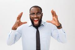 Retrato del varón negro enfadado desesperado que grita en la rabia y la cólera que rasgan su pelo hacia fuera mientras que siente fotos de archivo libres de regalías