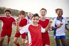 Retrato del varón y de los equipos de fútbol femeninos de la High School secundaria que celebran imagen de archivo