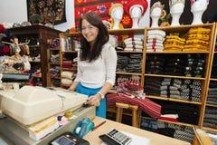 Retrato del vendedor de sexo femenino joven sonriente en el soporte del pago y envío en tienda de regalo fotografía de archivo
