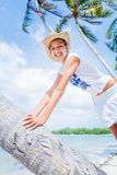 Retrato del verano de la chica joven bastante feliz Sonrisa y el sentarse en la palmera en la playa tropical de la isla con el cl Fotos de archivo libres de regalías