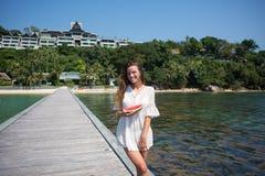 Retrato del verano de la moda de la mujer atractiva sana asombrosamente que presenta antes del océano azul en la isla exótica cal Fotografía de archivo libre de regalías