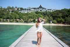 Retrato del verano de la moda de la mujer atractiva sana asombrosamente que presenta antes del océano azul en la isla exótica cal Imágenes de archivo libres de regalías