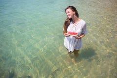 Retrato del verano de la moda de la mujer atractiva sana asombrosamente que presenta antes del océano azul en la isla exótica cal Foto de archivo libre de regalías