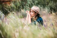 Retrato del verano de la mujer joven del inconformista que se sienta en una hierba el día soleado Imagen de archivo