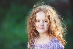 Retrato del verano de una muchacha de oro-cabelluda sonriente en el parque Imagenes de archivo